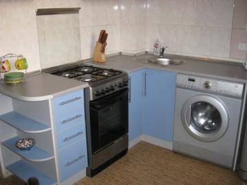 Стиральная машина стоит на кухне